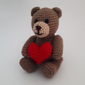 Crocheted teddy bear holding a big red heart