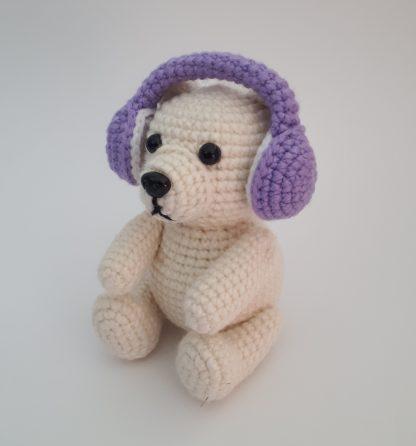 Crocheted polar bear wear a set of purple crocheted earmuffs.