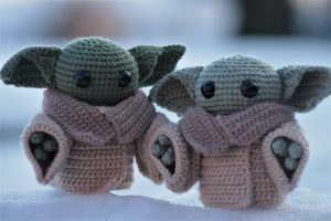 2 Baby Yoda Dolls standing upright in a snow bank